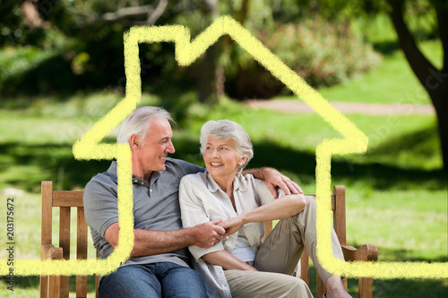 Senior couple sitting on a bench against house outline