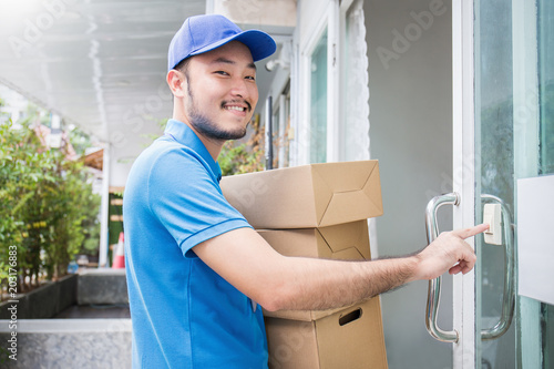 Valokuva  Portrait of happy delivery asian man with blue uniform hands holding cardboard b