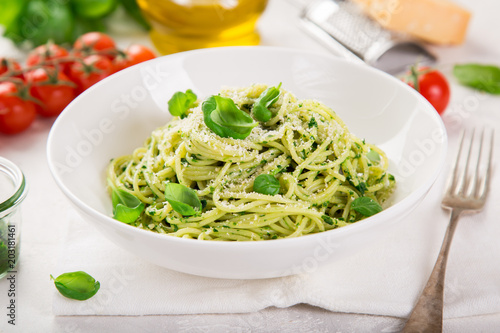 Photo  spaghetti pasta with basil pesto sauce and parmesan cheese on white bowl