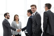 Business handshake. Two cheerful businessman shaking hands in o