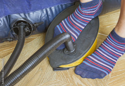 Photo A woman with air foot pump pumps an inflatable mattress or air bed at home