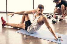 Handsome Sportsmen Stretching On Yoga Mat In Gym