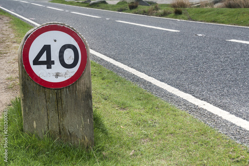 Fotografía  Speed limit sign on grass verge by side of road