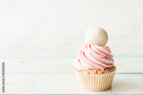Photo  One cupcake with macaroon on a wooden table. Copy space