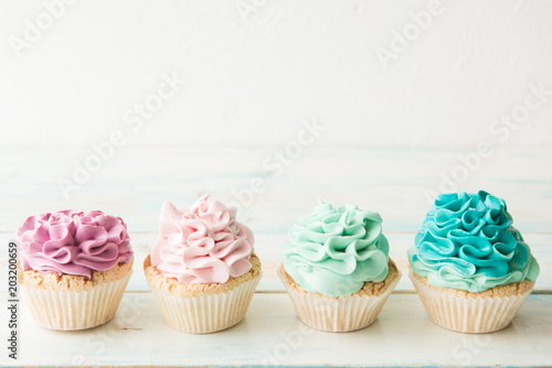 Photo Four colorful cupcakes on a light background. Copy space