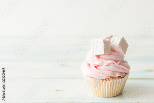 One cupcake on a wooden table. Copy space Wallpaper Mural