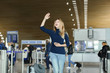 Woman standing at airport hall with smartphone, valise and raised hand. Concept of traveling, modern gadgets and positive emotions.