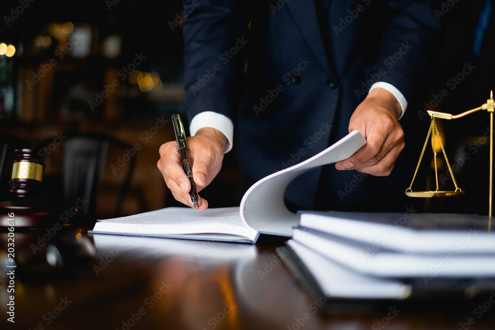 Fototapeta Close up lawyer businessman working or reading lawbook in office workplace for consultant lawyer concept.