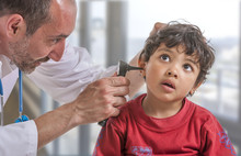 A Pediatrician Examining His Boy Patient's Ear At Doctor's Office
