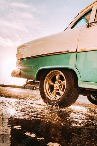 Retro car splashing puddle water