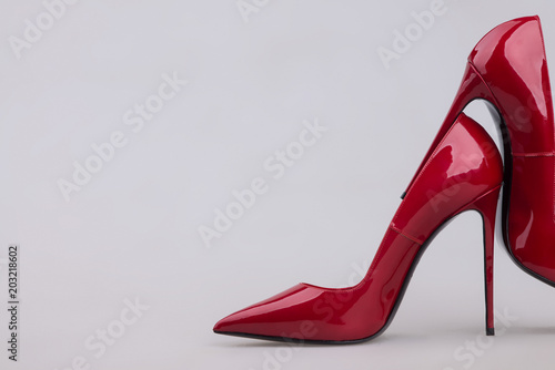 Obraz na plátne Women's red shoes with a varnish on a gray background