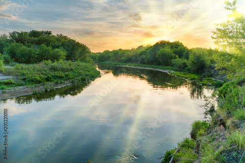 Printed kitchen splashbacks Beige Sunset over river. Landscape with green trees, dramatic sky, clouds, sun and sunrays