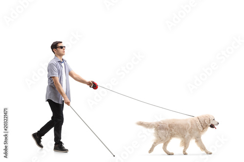 Blind young man walking with the help of a dog Canvas Print