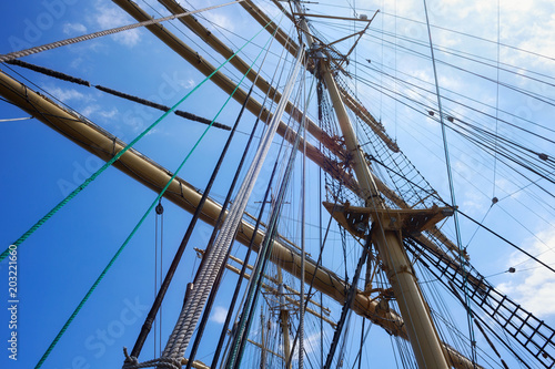 Foto op Canvas Schip Masts of a sailing ship with the lowered sails with blue sky on the background.