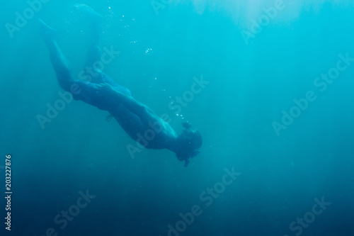 Young man free diver swimming in deep sea.