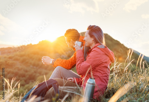 Happy traveler couple resting in the mountains at sunset.