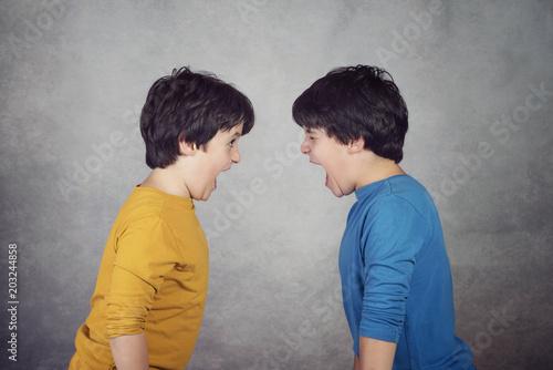 Fotografía  niños enfadados que gritan sobre fondo gris
