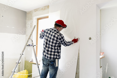 Glueing wallpapers at home. Young man, worker is putting up wallpapers on the wall. Home renovation concept