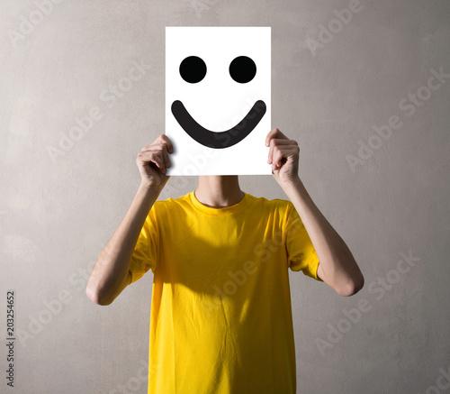 Photo persona che tiene davanti al viso un foglio felice