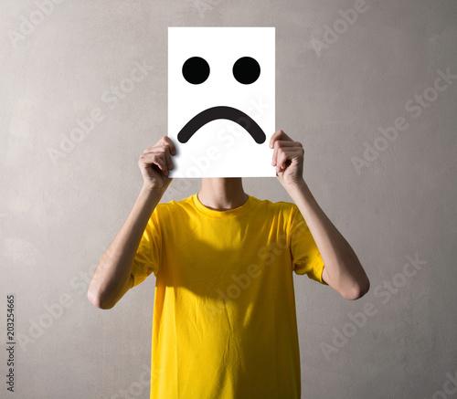Photo persona che tiene davanti al viso un foglio triste