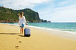 Young woman with her suitcase luggage on beautiful sandy beach w/ sea view on sunny day. Hipster female in loose cotton shirt on ocean shore having fun watching waves, sunbathing. Background, close up