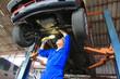 Car mechanic examining car using flashlight in auto repair service.