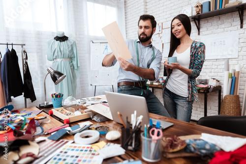 Two fashion designers looking at drawing talking. Slika na platnu
