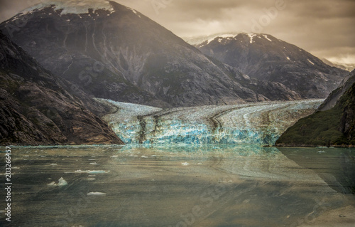 Foto op Canvas Gletsjers Glacier landscape with ocean and mountains on a cloudy sky in Alaska for global warming background