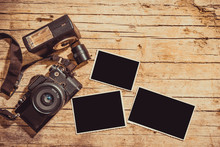 Vintage Film Camera And Two Blank Photo Frames On Wooden Table. Top View With Copy Space
