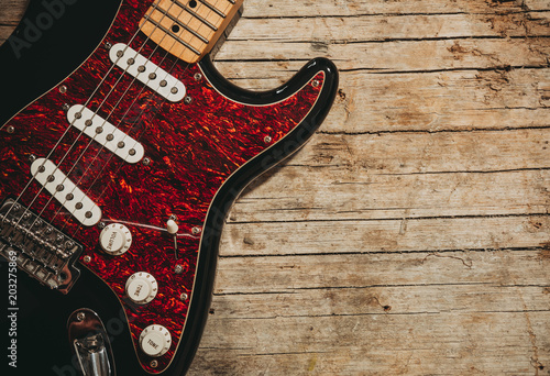 Papiers peints Peche Close-up of electric guitar lying on vintage wood background, with copy space