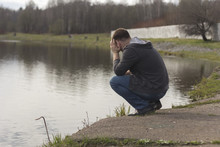 Sad Man Squatting At The River...