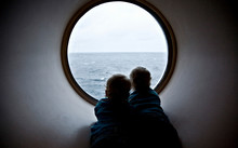 Two Children Are Looking Through The Porthole, The Ferry, The Autumn, The Baltic Sea
