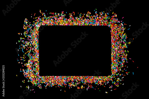 Border frame of colorful sprinkles on a black background with copy space Wallpaper Mural