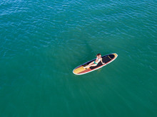 Nondescript Fit Female In A Bikini Lounging On Her SUP Stand Up Paddle Board In The Ocean From A Birds Eye View