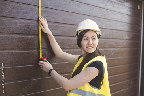 beautiful a woman in a helmet and in a construction waistcoat measuring a wall w Canvas Print