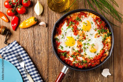 Photo sur Toile Plat cuisine Shakshouka, dish of eggs poached in a sauce of tomatoes, chili peppers, onions