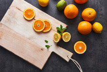 Flat Lay Of Fresh Citrus Fruits, Half Cut Orange And Lemons On Cutting Board On Black Stone Background. Copy Space. Horizontal Top View.