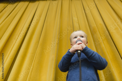 Low angle view of cute boy singing on microphone at stage against yellow curtains