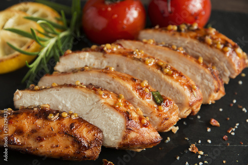 Fototapeta roasted cut chicken fillet breast with lemon tomato rosemary mustard seeds honey obraz