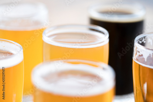 Платно Macro close up on a flight of craft beer in pint glasses