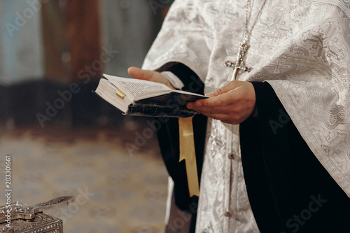 Fotografia Priest reading holy bible in christian church during orthodox wedding ceremony,