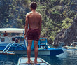Shirtless Asian guy standing on a bow of the ship on the background of a beautiful landscape of rocky bay.