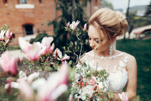 Glamourous Blonde Bride Posing Near Magnolia Flowers, Newlywed Bride Portrait - Beautiful Woman In White Dress Posing Near Floral Bush Outdoors