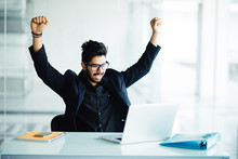Indian Young Bearded Businessman With Hands Stretched Pose While Working On Laptop, Celebrating Victory In Office