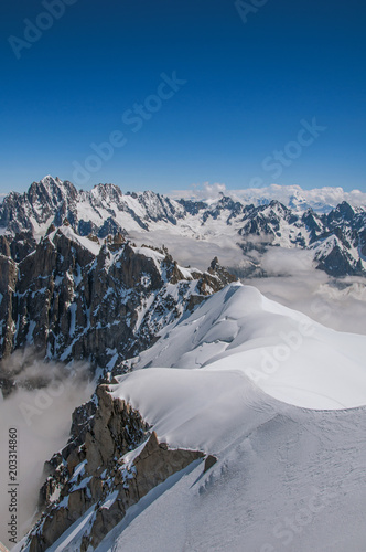 Tuinposter Alpen Snowy peaks and mountains in a sunny day, viewed from the Aiguille du Midi, near Chamonix. A famous ski resort located in Haute-Savoie Province, at the foot of Mont Blanc in the French Alps.