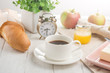 Morning cup of coffee, alarm clock, apples, butter and baguette, in a light kitchen. Background area, the concept of a bright morning and breakfast