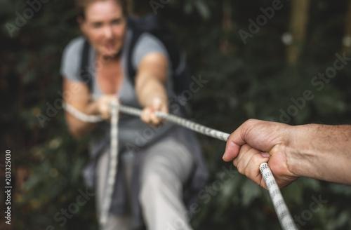 Fotografie, Obraz  Woman climbing up a rope