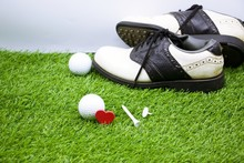 Golf Ball And Shoe Are On Gree...