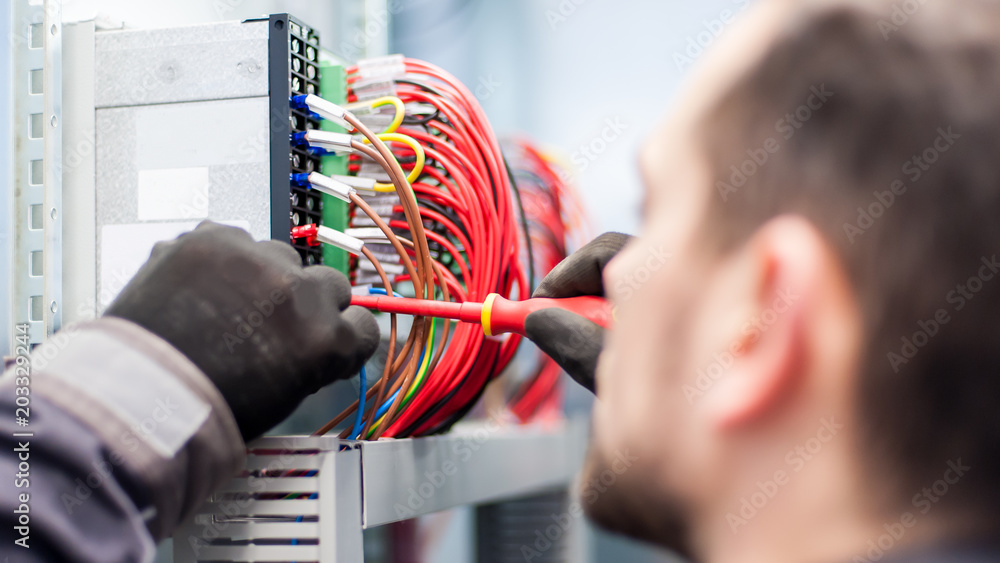 Fototapety, obrazy: Closeup of electrician engineer works with electric cable wires