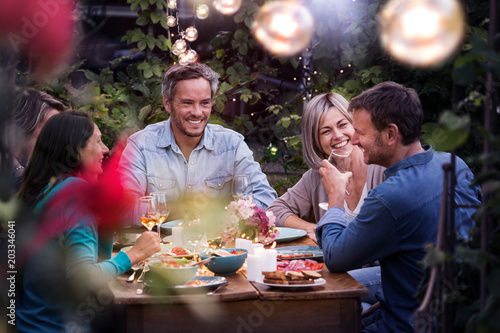 Fotomural Group of friends gathered around a table in a garden on a summer evening to shar